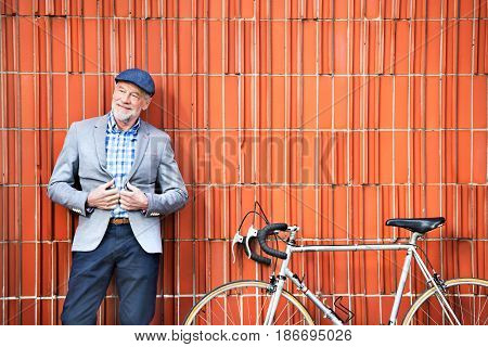 Handsome senior man in blue checked shirt and gray jacket with bicycle. Orange brick wall background.