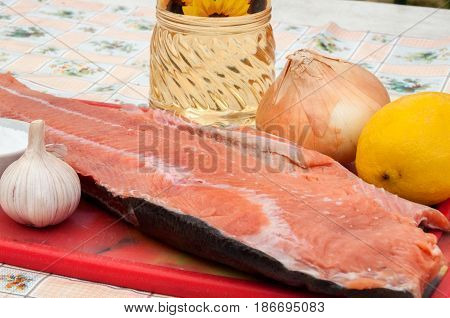 A piece of raw red fish with whole garlic lemon onion and a bottle of sunflower oil