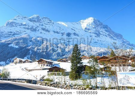Grindelwald Switzerland - April 29 2017: The Bernese Alps with blue sky viewed from Grindelwald Grund railway station with Swiss style houses on a foreground at Grindelwald Switzerland.