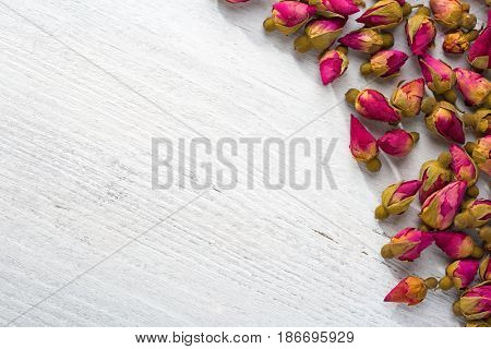 Dried buds of a tea rose on a  shabby wooden table. flat lay
