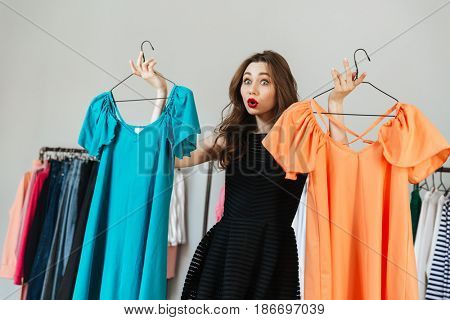 Photo of confused young woman standing in clothes shop indoors choosing between two dresses. Looking aside.