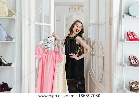 Image of young lady standing in clothes shop indoors holding dresses. Looking aside.