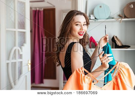 Image of young lady standing in clothes shop indoors choosing dresses. Looking at camera.