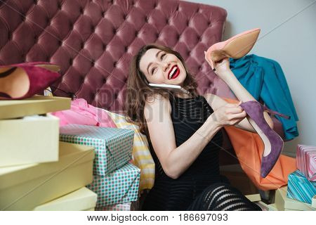 Image of happy young lady sitting on floor near sofa indoors choosing shoes while talking by phone. Looking aside.