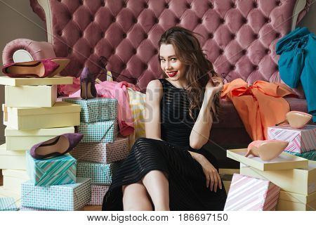 Image of happy young lady sitting on floor near sofa indoors choosing shoes. Looking at camera.