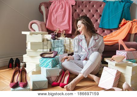 Image of happy young lady sitting on floor near sofa indoors choosing shoes. Looking aside.