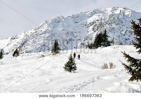 Mans hiking in the high winter mountain