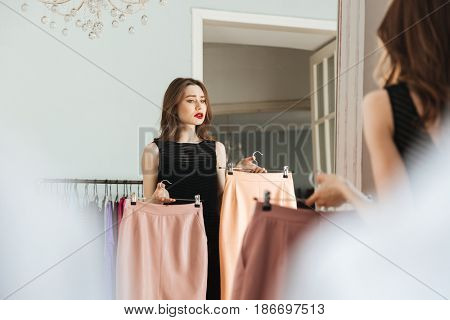 Picture of young concentrated woman standing in shop indoors choosing clothes. Looking aside.