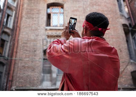 Back view portrait of a young african guy in headband taking picture with mobile phone outdoors
