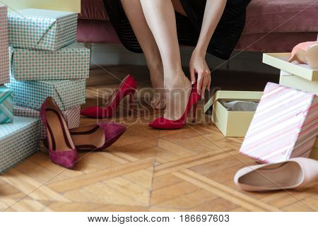 Cropped picture of young lady sitting on sofa indoors choosing shoes.