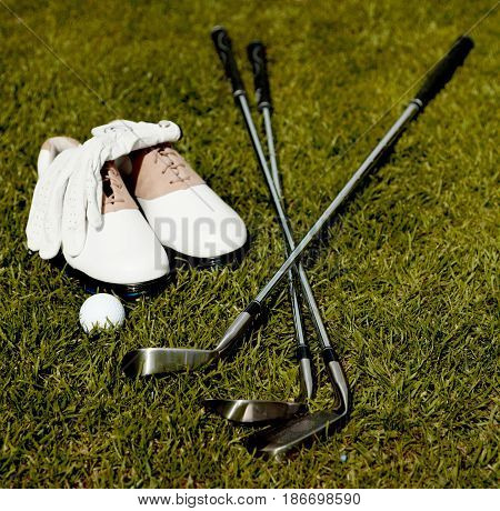 Golf ball close-up golf shoes golf clubs sport golf glove activity