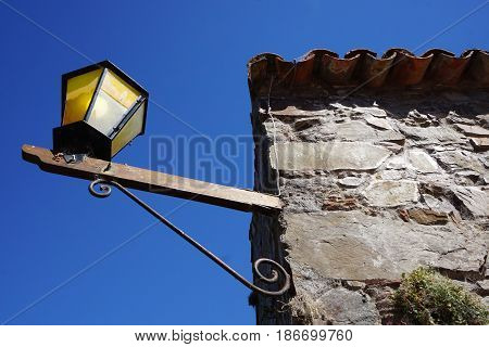 A light fixture attached to the outside of an old building against a blue sky