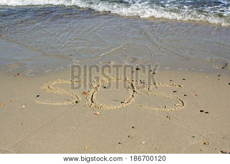 SOS - word drawn on the sand beach with the soft wave
