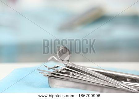 Dental tools in medical basin on table, closeup