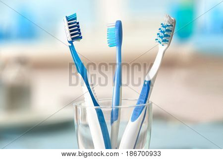 Toothbrushes in glass on blurred background