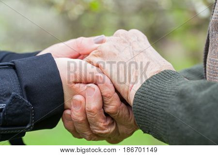 Close up picture of a young woman's hands holding an elderly female's hands