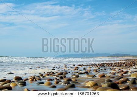 Sea shore with multitude of pebbles in the surf