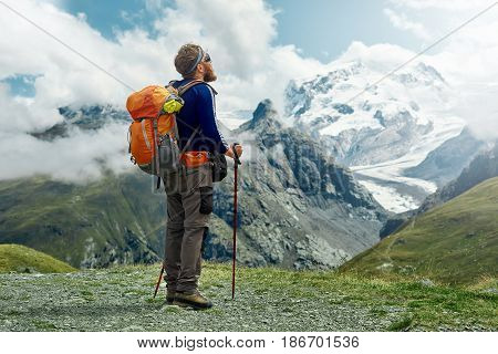 hiker with backpack stands on the trail in the Apls mountains. Trek near Matterhorn mount. Mountain ridge and blue sky on the background