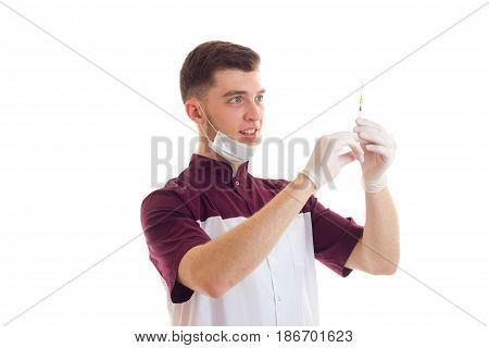young smiling laboratorian with the mask on the face lifted into the syringe is isolated on a white background