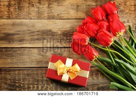 Bouquet of beautiful tulips and giftbox on wooden background