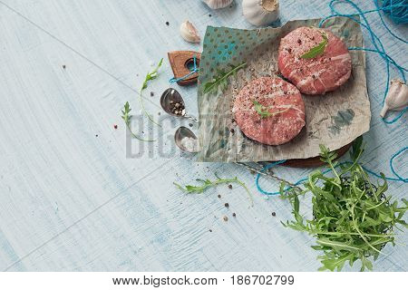 Organic raw ground beef wrapped in strips of bacon. Round patties for making homemade burger on wooden cutting board with herbs. Top view with space for text.