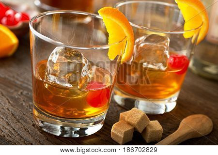 Delicious old fashioned cocktails with bourbon bitters sugar orange and maraschino cherry.