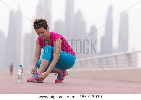 Young woman tying shoelaces on sneakers on a promenade with a big city in the background. Standing next to a bottle of water. Exercise outdoors