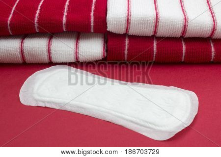 Terry bath red towels and menstruation sanitary soft cotton daily pad for woman hygiene protection. Woman critical days gynecological menstruation cycle blood period