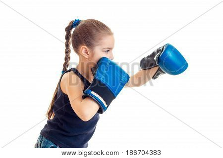 the little child is standing sideways in front of the camera and reaches out his hands in boxing gloves is isolated on a white background