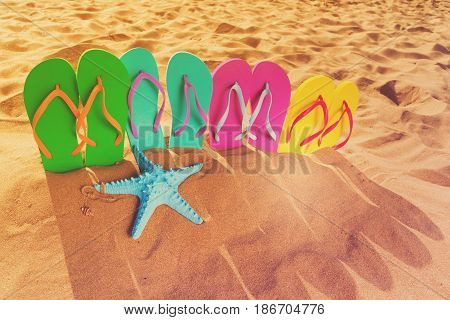 Summer beach fun - set of family sandals in sand on beach, retro toned