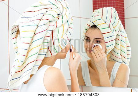 beautiful girl with towel on hair rubs face with a cotton disk in front of the mirror close-up