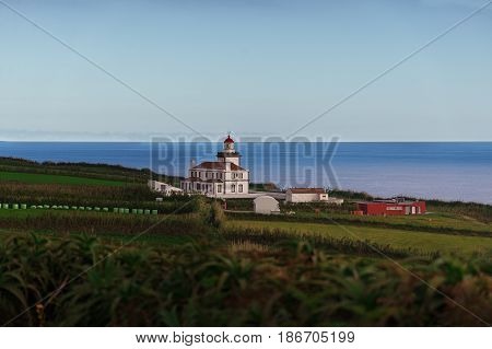 The lighthouse standing on the shore of the Atlantic ocean and showing the way for the ships