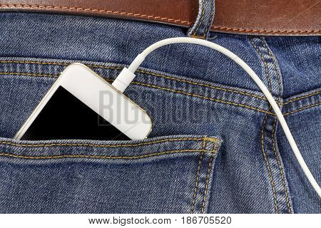 Smartphone With Connection Usb Cable In The Back Pocket Of The Jeans Closeup