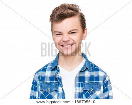 Teen boy making silly grimace - expressing disgust face. Upset child isolated on white background. Emotional portrait of caucasian teenager looking at camera.
