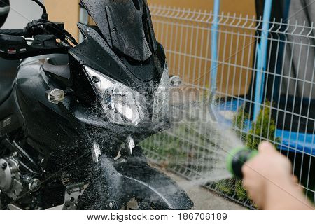 Cleaning modern black touristic motorbike with water