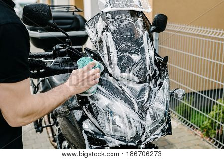 Cleaning Black Touristic Motorbike With Water