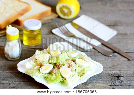 Home salad with napa cabbage, quail eggs and canned tuna fish. Tasty salad on a plate, fork, knife, olive oil bottle, salt shaker, bread slices on rustic wooden table. Healthy starter food. Closeup