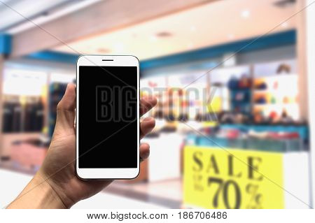 holding the mobile phone on a blurry background.