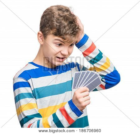 Emotional portrait of caucasian teen boy with gamble cards. Surprised or shocked teenager looking at collect cards. Funny teenager playing, on white background. Concept - free time, fun and hobby.