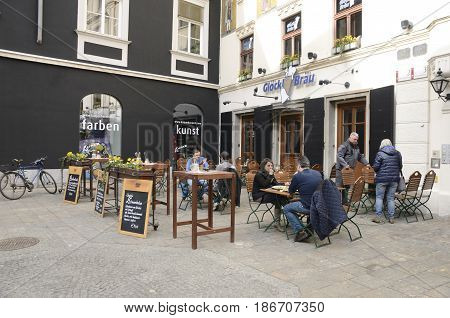 GRAZ, AUSTRIA - MARCH 19, 2017: People at outdoor restaurant on Glockenspielplatz square in Graz the capital of federal state of Styria Austria.