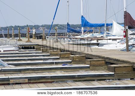 Boats in their slips on a long pier at a lake.