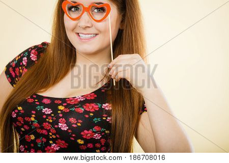 Happy woman holding fake eyeglasses on stick having fun. Photo and carnival funny accessories concept.