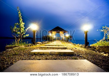 Stone path with lights leading to a shelter. Set against the blue evening sky and green plants