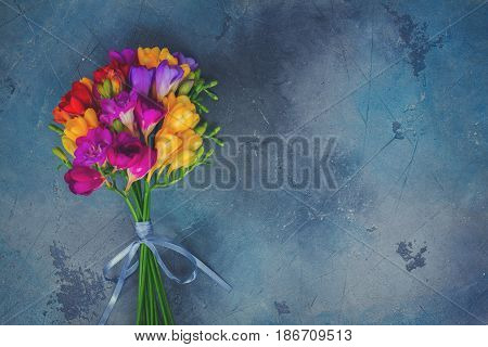 Posy of fresh freesia flowers on gray stone background with copy space, retro toned