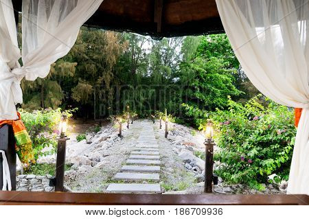 Open white curtains leading to a stone path with lights and bushes surrounding it. Perfect for a vacation