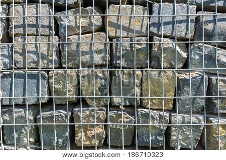 Close-up of a Stones behind Bars. Big Stones. Close-up of  a stacked Stones. Geology. Grey Stones
