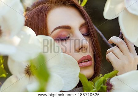 Portrait of young beautiful woman posing among blooming trees with pink eyeshadow. Spring look on magnolias background.
