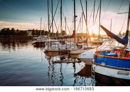 Riga, Latvia - July 1, 2016: Riga, Latvia. Many Yachts Moored At The City Pier Harbour Bay And Quay In Summer Sunny Evening. Reflections From Boats In Water Of Western Dvina River.