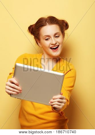 young woman with tablet pc over yellow background
