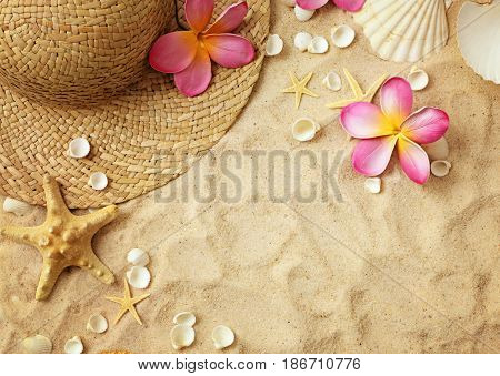 summer hat and seashells on sand. summer frame background